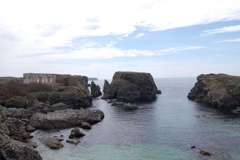 Rocks in calm sea against sky