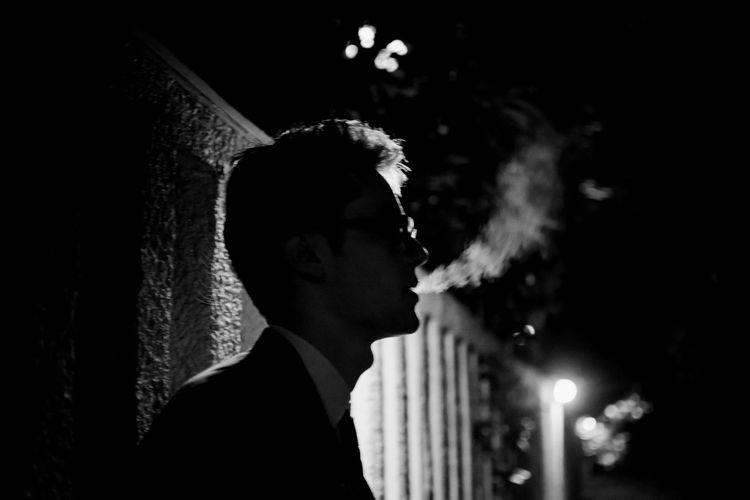 Side view of man smoking at night
