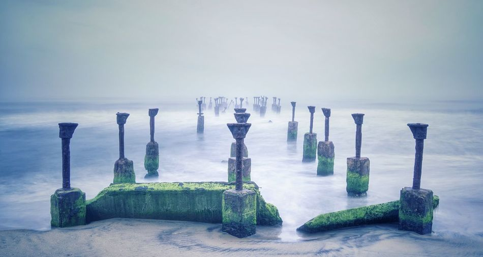 Old broken bridge in sea against sky during foggy weather