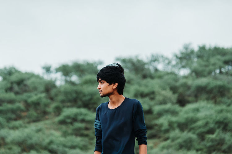 Young man looking away while standing against trees