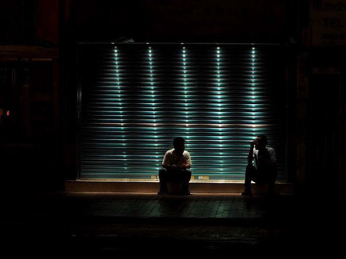 Men sitting against illuminated shutter in city at night