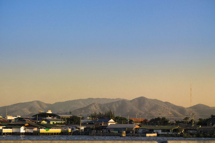 Sailboats in city by mountains against clear sky