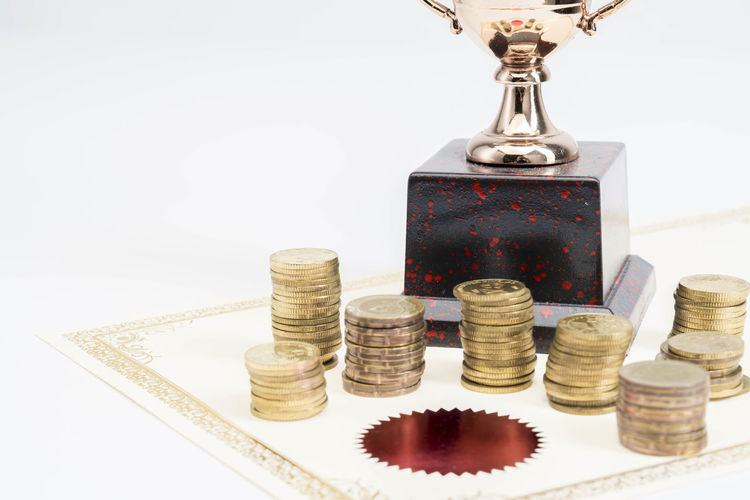 Trophy Cup and coins and blank certificate on white background Still Life Indoors  Coin Stack Business Large Group Of Objects Studio Shot White Background Finance No People Wealth Savings Investment Success Close-up Development Table Currency Metal Achievement Economy Silver Colored