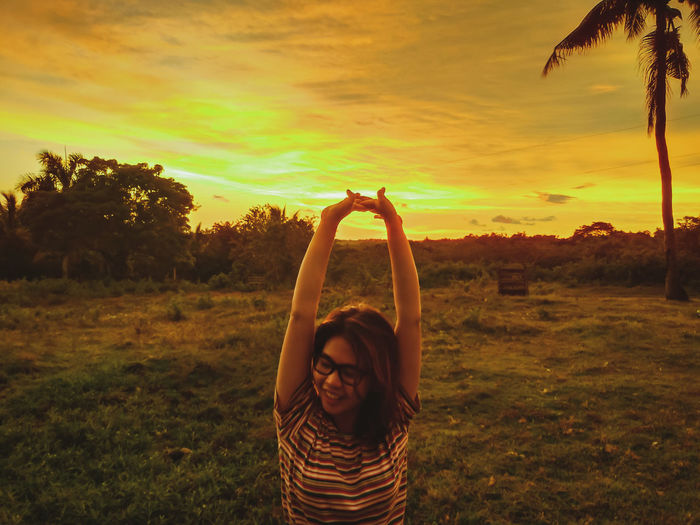Portrait of woman with arms raised on field against sky during sunset