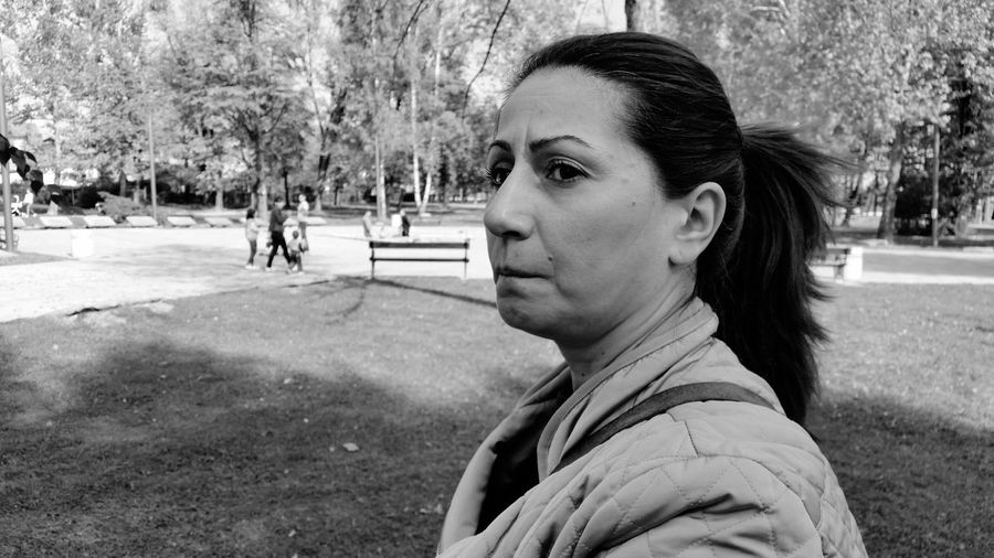 Close-up of mature woman looking away while standing at park