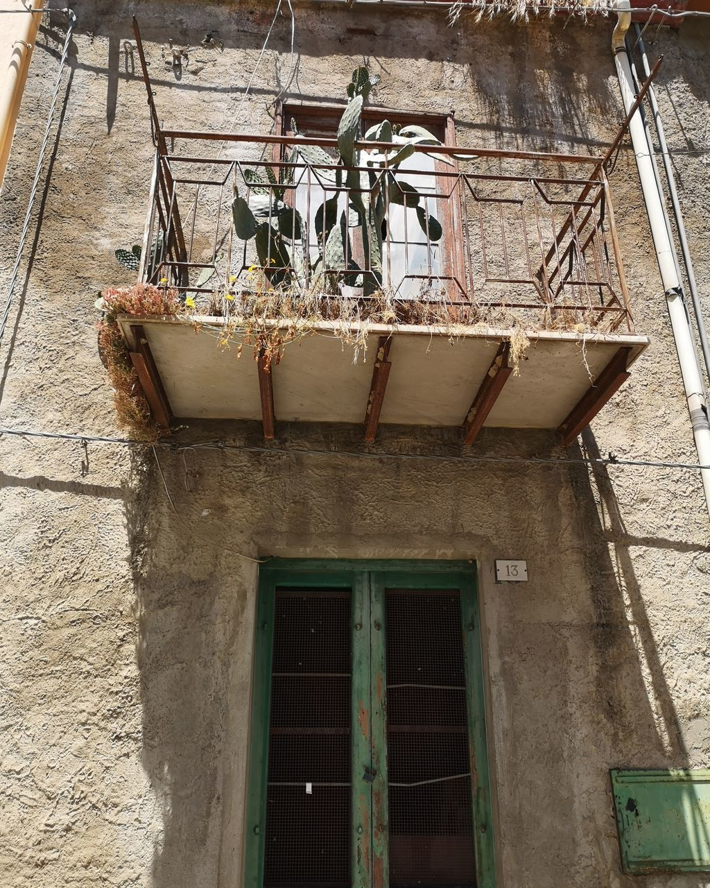 LOW ANGLE VIEW OF WINDOW HANGING ON OLD BUILDING