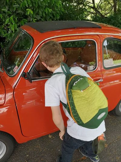 Interesting Reflection Boy Car Casual Clothing Child Day Design Fascination Glass Leisure Activity Lifestyles Mode Of Transportation Motor Vehicle One Person Outdoors Real People Red Car Red Color Retro Styled Three Quarter Length Transportation Vintage Vintage Cars