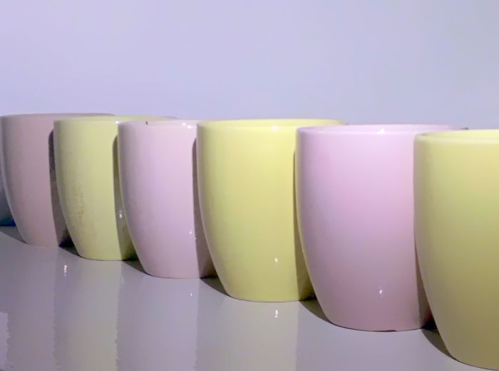 Close-Up Of Pink And Yellow Cups Arranged In Row On Table