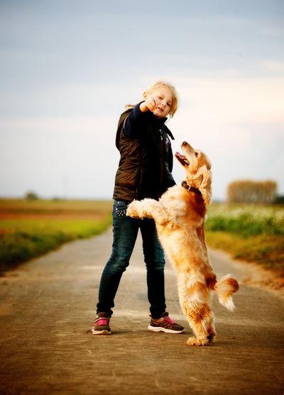 Full Length Of Girl With Dog Against Sky
