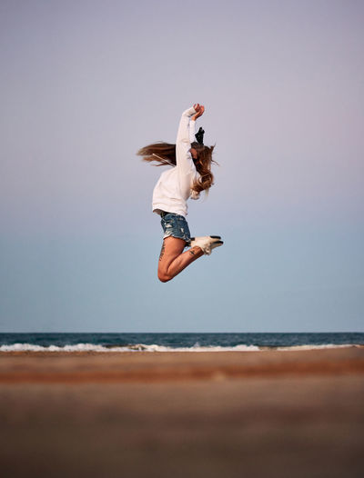 Low angle view of person jumping on beach against clear sky