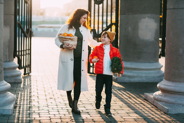 A beautiful mother with her son in a bright orange jacket and a fashionable yellow hat