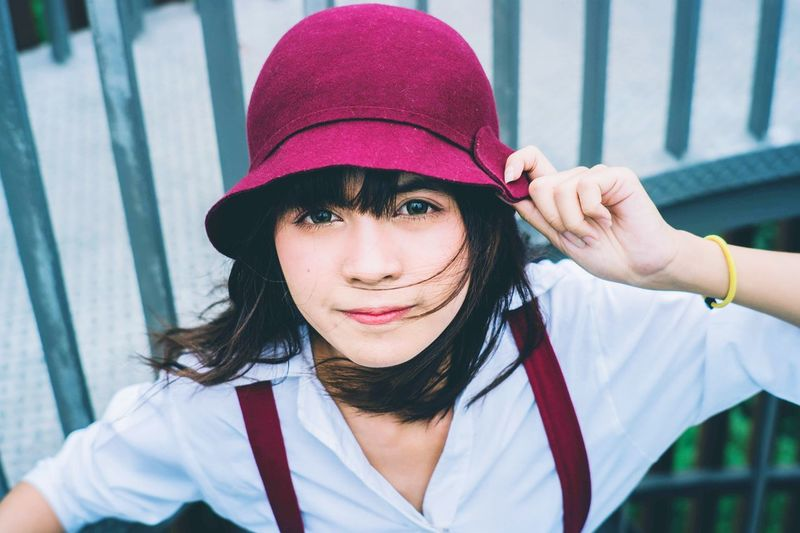 High angle portrait of young woman wearing hat outdoors