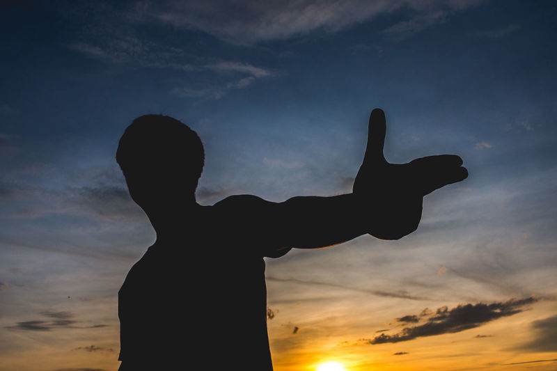 Silhouette man gesturing against sky during sunset