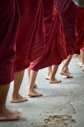 Low section of monks walking on footpath
