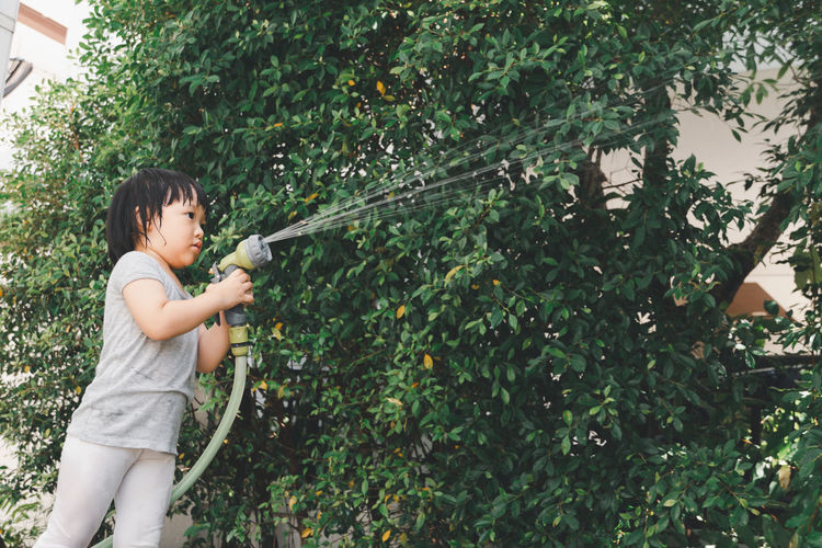 Funny moment of 3 year old asian kid playing water with garden hose in backyard.