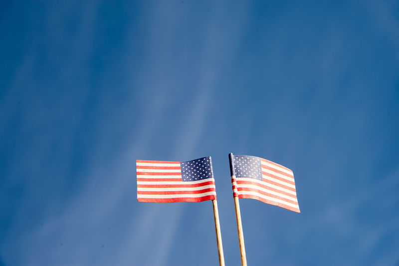 Low angle view of small american flags against blue sky