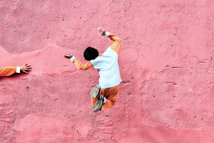 Full length of boy jumping in mid-air against pink wall