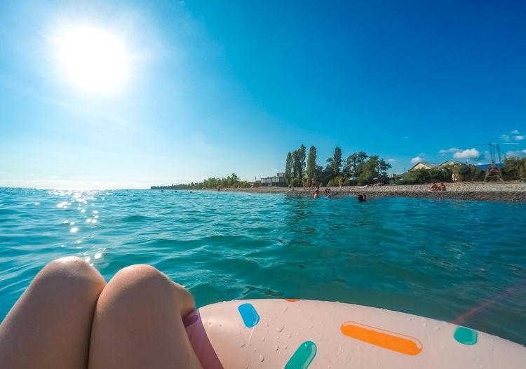 Girls legs on a swim tube in the black sea