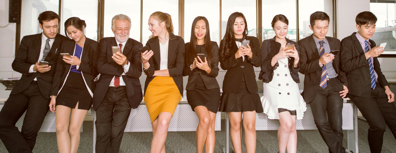 Business People Using Smart Phones By Window In Office