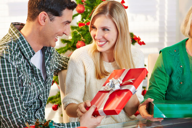 Happy Family Sitting On Chair By Table At Home During Christmas