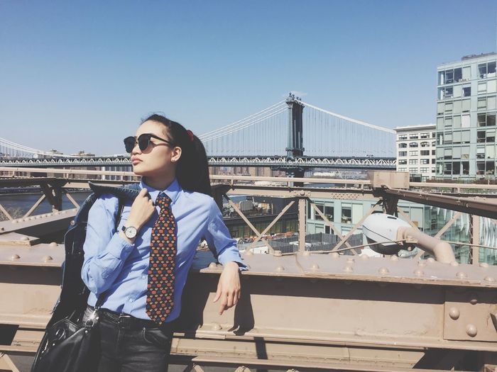 Businesswoman standing on brooklyn bridge against sky in city