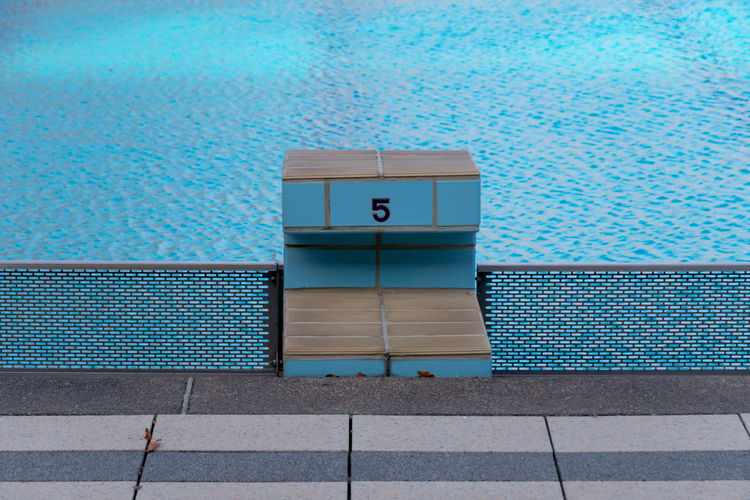 High angle view of number 5 on starting block at swimming pool