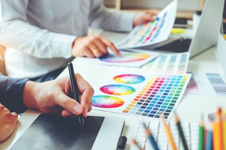 Design professional pointing at color swatch on table
