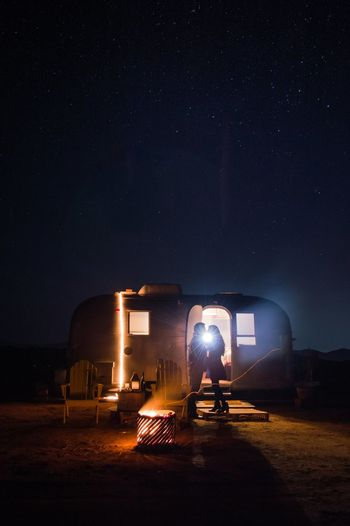 Back lit couple standing at campsite against sky at night