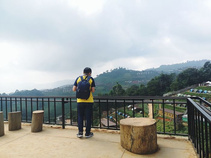 Rear view of man standing on railing against mountain