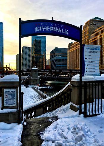 Snow covering urban landscape of Chicago Loop after winter storm, while sun sets over entrance to the riverwalk at Chicago River. Chicago Chicago River Chicago Riverwalk Chicago Loop Downtown Chicago Gate Restaurants Sign Architecture Bannister Bridge - Man Made Structure Building Exterior Built Structure City Cityscape Cold Temperature Crane - Construction Machinery Handicapped Sign Ledge Sky Skyscraper Snow Sunset Weather Winter