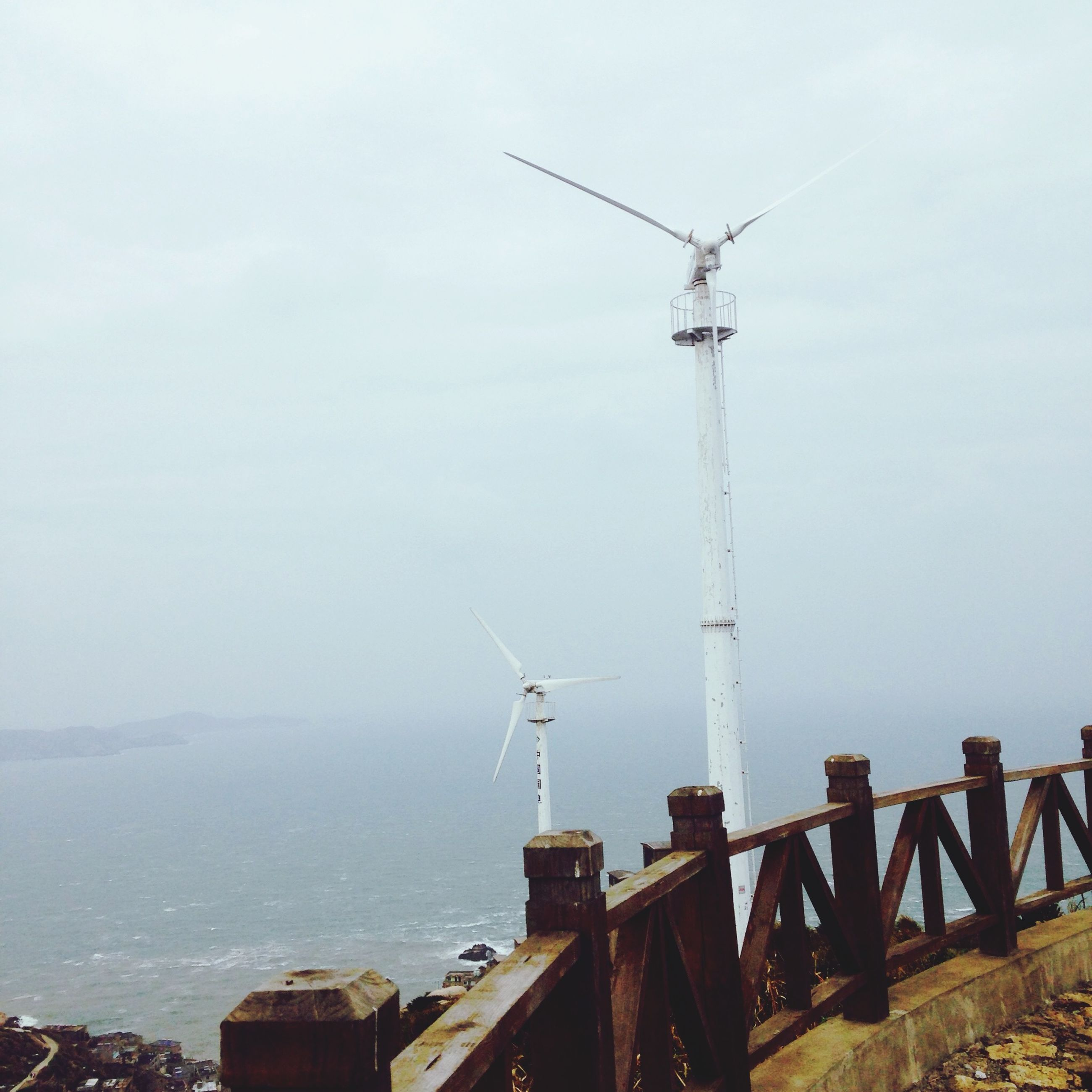 sea, water, renewable energy, fuel and power generation, wind turbine, sky, alternative energy, wind power, environmental conservation, crane - construction machinery, windmill, technology, built structure, day, industry, building exterior, nature, commercial dock, traditional windmill, architecture