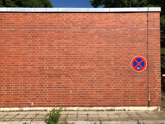 Road sign against brick wall