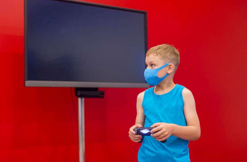 Boy playing video game against red background