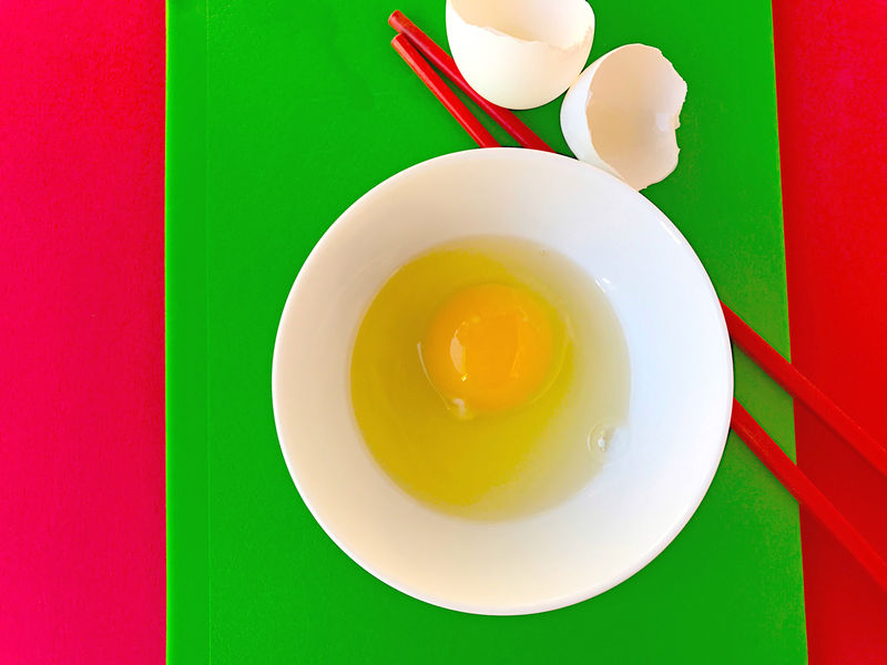 Bowl with egg on red and green Bowl Chopsticks Close-up Colorful Contrasts Cutting Boards Day Egg Eggshells Food Green Indoors  Natural Light No People Overhead Phone Camera Red Saturated Colors Simple Uncluttered White