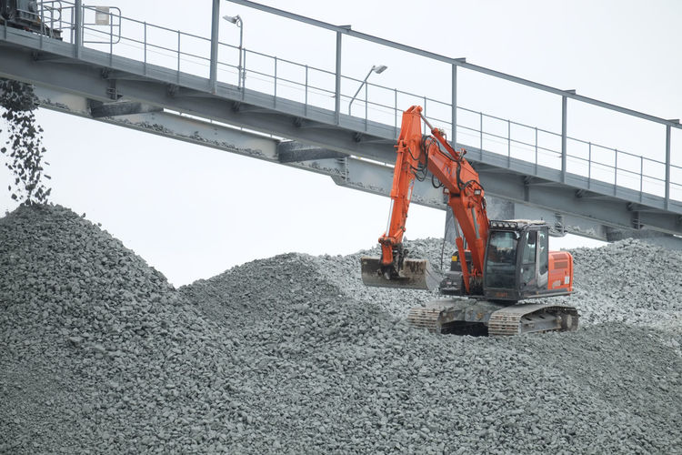 Doel, Antwerp, Belgium – February 2019: Red crane on a huge pile of gravel working to put the gravel on a transporting conveyor Machinery Industry Transportation Construction Industry Construction Machinery Construction Site Sky Development Nature Day Heap Earth Mover Land Vehicle Mode Of Transportation Bulldozer Outdoors Equipment Mining Land No People Industrial Equipment