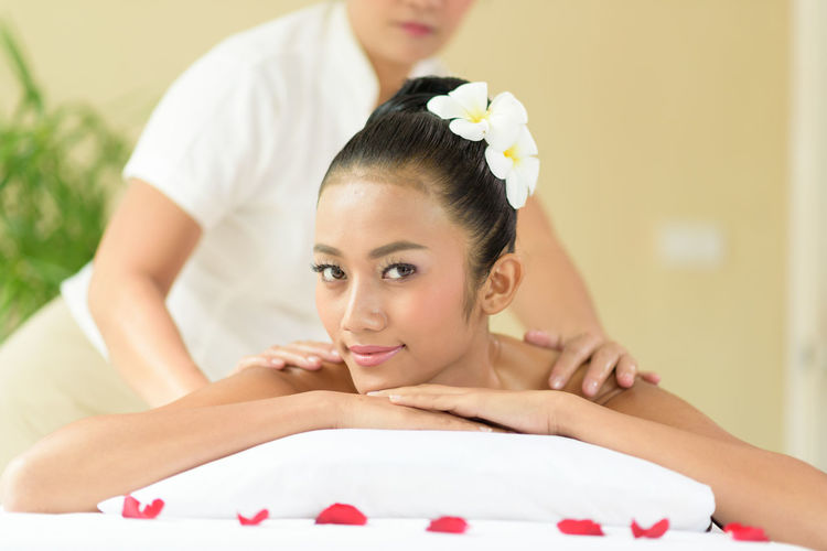 Midsection Of Masseuse Giving Massage To Young Woman Relaxing At Spa