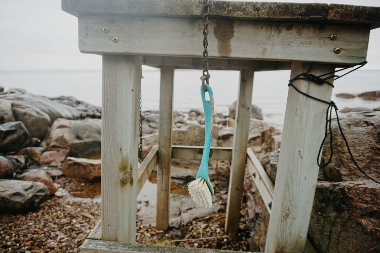 Cleaning brush hanging on a wooden table Cleaning Cleaning Equipment Fishing Village Rustic Stones And Water Beach Brush Cleaning Brush Fishing Fishing Time Outdoors Stones And Pebbles Table Wood - Material