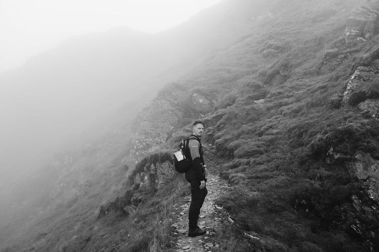 Man standing on mountain during foggy weather