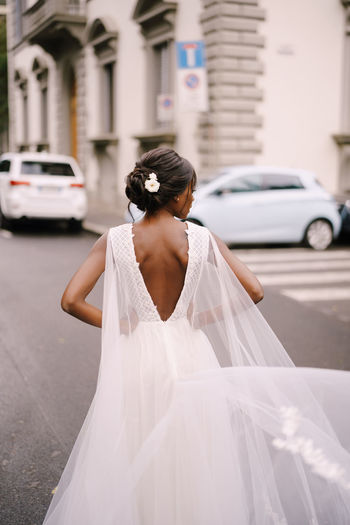 Rear view of bride standing on road