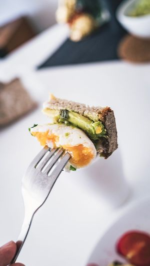 Avocado Poached Egg Toast Healthy Eating Breakfast Toasted Bread Avocado Hipster Close-up Hand Human Hand Human Body Part Real People One Person Holding Food Fork Food And Drink Freshness Eating Utensil Lifestyles Finger Ready-to-eat Focus On Foreground