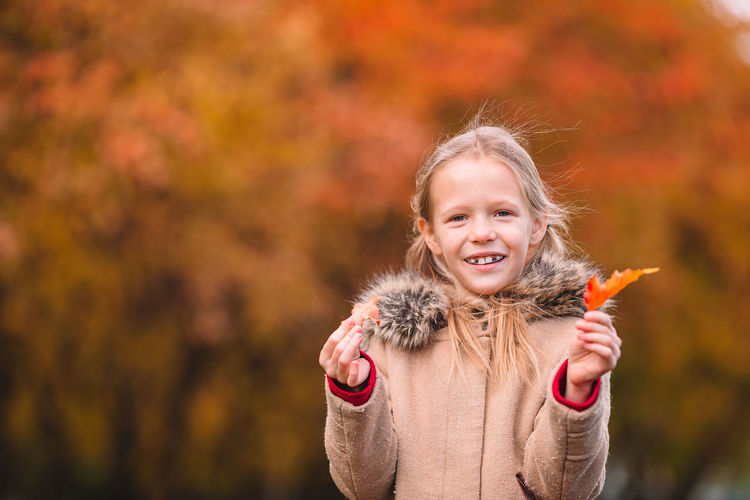 Portrait of smiling girl with autumn leaf