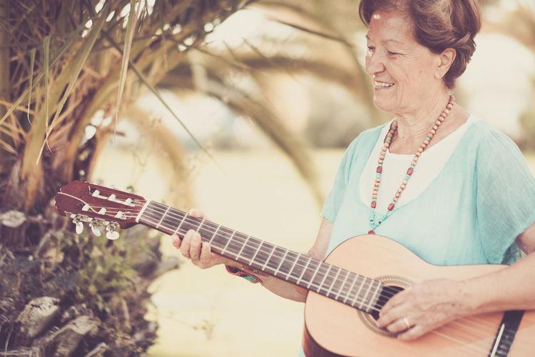 Happy senior woman playing guitar