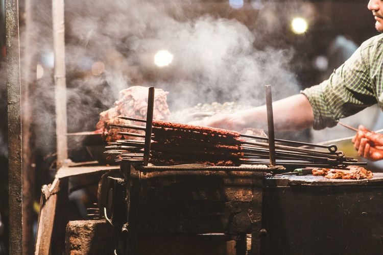Man cooking meat at market stall