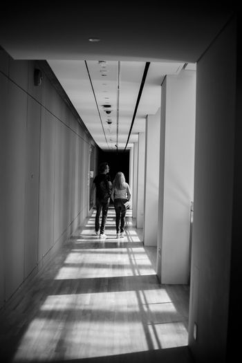 Rear view of men walking in corridor