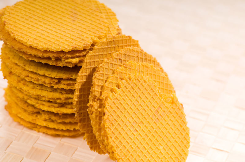 Many orange colour wafers stack lying on beige mat on table. Food snack prepared and ready to eat, standing on mat, zoom, horizontal orientation, objects in studio shot. Baked Biscuit Cheesey Cheesy Close-up Cookie Crisp Crispy Crunch Crunchy Dry Flat Flavour Food No People Pile Roasted Snack Snacks Stack Tasty Thin Tidbits Wafer Waffers