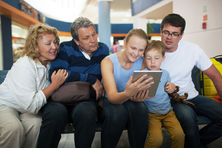 Happy family looking at digital tablet while sitting at airport terminal
