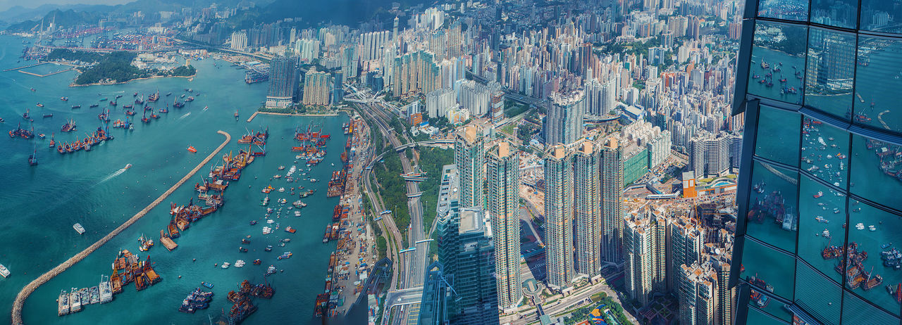 Panoramic Shot Of Victoria Harbour By Modern Buildings In City