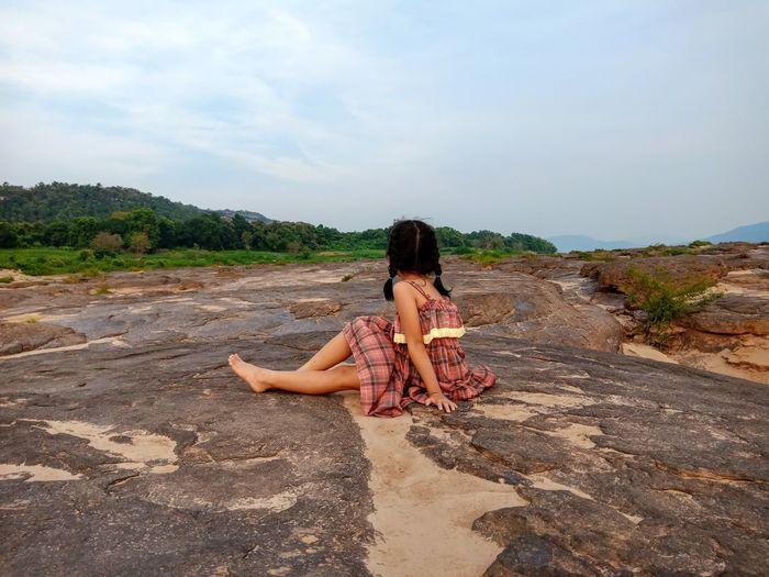 Girl sitting on rock against sky
