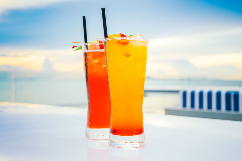 Alcohol Beach Close-up Cocktail Cold Temperature Day Drink Drinking Glass Drinking Straw Focus On Foreground Food And Drink Freshness Liqueur Nature No People Orange Color Orange Juice  Outdoors Red Refreshment Sea Sky Table Tropical Drink Yellow