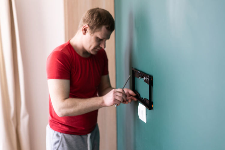 Side view of young man standing against wall at home